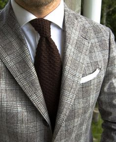 Light grey plaid jacket, white shirt with grey dress stripes, brown knitted tie