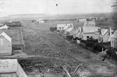 Looking west along Armagh Street in Christchurch, May 1860. Riccarton bush is in the left background. The long building with three dormers, ...
