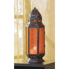 TALL MOROCCAN-STYLE CANDLE LANTERN Lead your mind to far-off adventures! Amber glass panels reflect the flame of a single candle to create shadows that ripple and move in an endlessly enthralling pattern.   $29.95