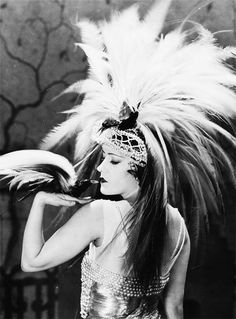 Gloria Swanson-1920's. I like the pose due to the fact she has a bird prop on her arm and a head dress to match the feathers on the bird. The model looks as if she is meant to be in this type of habitat.