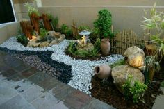 Jardin con decoraciones adicionales tales comi el agua saliendo del bambu, piedras blancas y negras, piedras de mar, rocas y adornos.