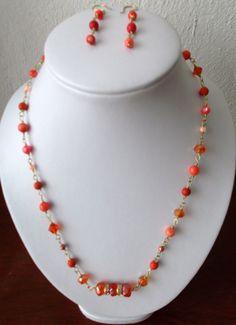Collar en cuentas color coral, con detalles dorados..