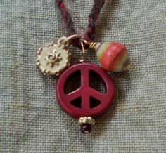 The peace sign dates to 1958, when British artist and activist Gerard Holtom designed the now- familiar symbol for use at a rally calling for nuclear disarmament.     Mothers' cooperatives in Uganda make these paper beads out of pages from discarded magazines.     The spiral (oxidized brass) symbolizes our understanding and acceptance of change and evolution in our lives.    Muted chocolate and deep crimson recycled cashmere cord is hand-crocheted.