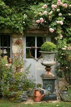 French copper watering can and medici urn on pedestal climbing rose rustic…