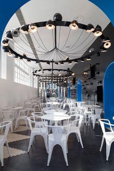 foorni.pl | Restauracja księgarni Oxford w Indiach – biały, czarny, niebieski, białe metalowe krzesła, biały metalowy stół, czarna ściana, duży czarny okrągły żyrandol