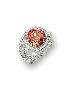 PADPARADSCHA AND DIAMOND RING.  Centring on a modified brilliant-cut padparadscha sapphire weighing 11.51 carats, framed by brilliant-cut diamonds extending to the stylised shoulders, the diamonds together weighing approximately 1.55 carats, mounted in platinum.