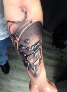 Electric guitar tattoo on the arm. The electric guitar is seen to have its cord plugged in presuming it is connected to an amp to make it sound even better. The light shading on the guitar also does wonders to the soft vibe of the design.