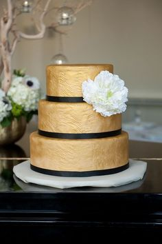 Textured gold wedding cake trimmed with black ribbon | Photo by Mikkel Paige | Cake design by So Simply Sweet