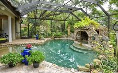 Glass-covered pool, hot tub, patio and gardens extending directly off the home. Hot tub enclosed in a stone cave. Gardens and plants surround the pool giving it an oasis-like environment.
