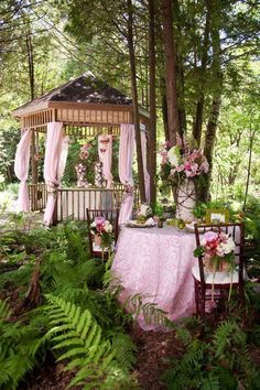 Beautiful Garden party in the forest with an ornate wood gazebo adorned with pink curtains.  In the path is a lovely table and chairs decorated with pink and flowers ready for fun!