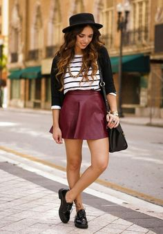 A Striped Shirt With A Black Cardigan And A Burgundy Leather Skirt, Accessorized With a Solid Black Bag With A Black Fedora And A Pair Of Black Oxfords