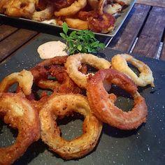Prepara aros de cebolla en casa muy crujientes con esta detallada receta del blog EL RITMO EN LOS FOGONES. También se da la receta de una salsa para acompañarlos.