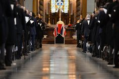 THATCHER FUNERAL: Mourners stood during a funeral for former British Prime Minister Margaret Thatcher in St. Paul's Cathedral in London on Wednesday. The coffin, center, was draped with a flag. (Ben Stansall/AFP/Getty Images)