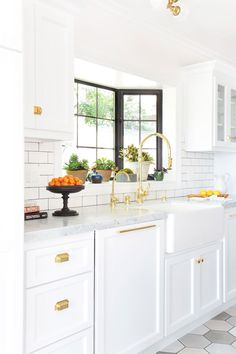 All white and brass kitchen with shaker cabinets and hexagon floor tiles.