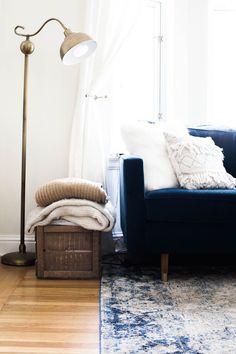 Canapé indigo et douceur des textiles clairs + mélange de matières : velour, laine, cuivre, bois, lin...le bon mix !