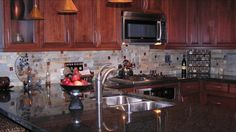 Love everything about this! Impala black granite medium cherry cabinets with chocolate glaze, stone backsplash and stainless sink and appliances. Perfect.