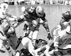 Black and white photo of University of Oregon tailback Derek Loville, #32, plunging through a hole created by the offensive line, including fullback Latin Berry, #42, and tackle Rick Hunt, #57, during a 1988 game versus Stanford at Autzen Stadium and won by the Ducks 7-3. ©University of Oregon Libraries - Special Collections and University Archives