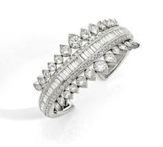 Suzanne BELPERRON  BRACELET RIGIDE OUVRANT  En or gris 18k (750), formé d'un bandeau biseauté en chute, orné d'une ligne de diamants taillés en baguette entre deux lignes de diamants taillés en brillant, dans sa partie supérieure, souligné de part et d'autre d'une chute de motifs piriformes sertis chacun de deux diamants taillés en brillant  Exécuté entre 1942 et 1955  Poinçons de Gröené et Darde (poinçon partiellement effacé). 15 cm; poids brut : 46,9 g  Cert OB.