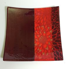 This platter has a section of transparent red-orange glass bordered by opaque deep red glass, and features our dahlia drawing printed in bright red and yellow enamels, then fused in a kiln to about 14