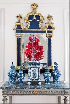 red french tulips in a tuliper positioned in front of a beautiful blue gilt mirror and surrounded by blue & white porcelain vases.