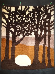A large 70s vintage latch hook wall hanging, or rug, with dark brown trees silhouetted against an earth toned background. Well made and in excellent vintage condition, the unused mesh border is simply folded over and loosely basted to the underside and there are three very simple hanging loops on the top that could accommodate a doweling rod.  A strong piece of focal art. (I have more latch hook pieces here…