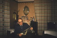 Colour transparency of John Wills' grandfather sitting in an armchair in the 'dining room' (which was actually the living room) at Mill House, the home of the Wills family from 1927 to 1992. The photograph was probably taken by John Wills' father around 1956. It is a Kodachrome 40 mm transparency housed in a cardboard holder. This is one item in the Documenting Homes collection (477/2012-1 to -16) from John Wills.