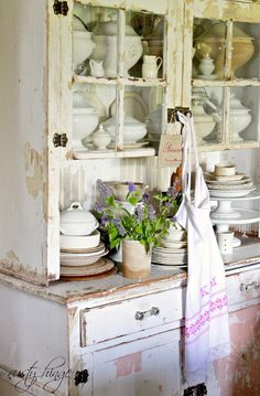 The kitchen hutch is filled with antique French ironstone!