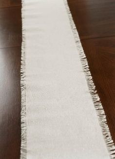 """Fringed Edge Linen Table Runner 108in..  $5.99...  This elegantly rustic runner adds luxury to long, dark wood dining tables. Create an awe inspiring decor for a seasonal feast by scattering candles, vases of flowers, and small ornaments on the Fringed Linen Table Runner. Its long, broad design adds depth and dimension to table centerpieces for any occasion. This piece measures 8"""" wide and 108"""" long. The fringe is approximately 5/8"""" wide."""