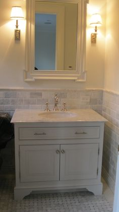 Furniture feet on vanity cabinet. Also love the marble subway tiles.