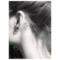 Small rose tattoo behind the left ear. Tattoo artist: Dr. Woo