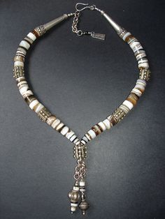 Designed by Luda Hunter   Necklace combining Old rare Tibetan Banded Agate wheels with handmade old Ethiopian metal beads and Afghan slver beads. Finished with new Bali 9.25 sterling silver cones and clasp.