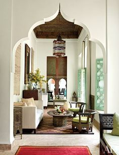 Moorish arches make for striking doorways inside the Marrakech home. At one end of the living room, a table draped with a Kurdish kilim from Iran faces a Syrian daybed and star-shaped side table; the rugs are Moroccan.