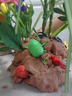 For your #Insect Unit: chocolate play-doh, plastic bugs, and fake flowers. Could also add pebbles/small rocks and twigs! From: EngagingPreschoolMinds.blogspot.com
