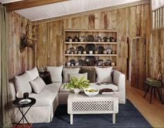 I love the rustic wood paneling/white furniture combo... the deer trophy, not so much!