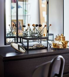 Makeup accessories, perfume and jewelry are on display on top of a chest of drawers.