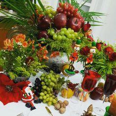 Arranjo natalino  com muitas frutas da época e flores