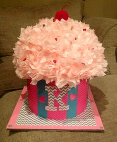 Cupcake Valentine Box! -used a hat box -styrofoam half sphere -covered it with tissue paper squares attached with straight pins -clown nose for cherry -added a red covered wire for stem -covered with scrapbook paper