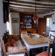 The kitchen/dining room is furnished with a Welsh dresser, a large kitchen table, and a wooden sofa covered in cushions.