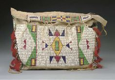 A Sioux beaded hide possible bag. Sinew sewn and lane-stitched in classic colors, decorated with typical geometric motifs on the front, bars alternating with stripes on the sides, and rectangular motifs centering a cross on the flap. Trimmed with pairs of metal cones inserted with red-dyed horsehair, hide ties.