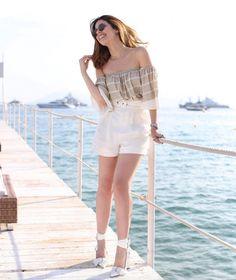 Camila Coutinho com short branco e blusa ombro a ombro em Cannes, durante o festival de cinema.