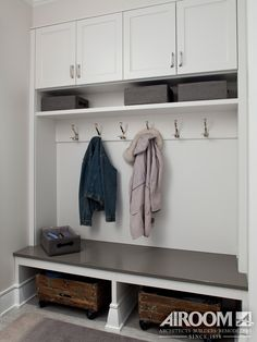 A modern mudroom organizer from a home remodel in Winnetka, IL. The organizer is complete with coat hooks and custom white storage cabinets | Airoom | www.Airoom.com