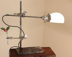 Lampe industrielle fait avec un pied de lampe à l'huile antique, un millésime filtre erlenmeyer de 500ml, un centrifugeuse tube vase en verre (avec bouchon rodé) et d'autres équipements de laboratoire récupéré. Livré avec une ampoule de candélabres de style Edison 25W nostalgique, douille candélabre en porcelaine, cordon noir recouvert de tissu et un interrupteur à tirette lourds. Un accent rare pour n'importe quel support bureau, commode ou de la nuit. 13 pouces de hauteur.  ** Pour les…