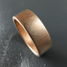 Rose gold handmade wedding band by Spexton in 7MM width with a brushed finish. Easy to maintain, and seamless construction.