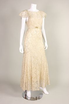 1930's Lamé Lace Ivory Bias-Cut Gown is made of metallic lamé ivory lace in a floral pattern. It is cut on the bias for that timeless 1930's silhouette. Flounce sleeves. V-neck back. Side snap closures. Unlined, but comes with an ivory silk slip. Detached belt with brass-toned filigree hardware.