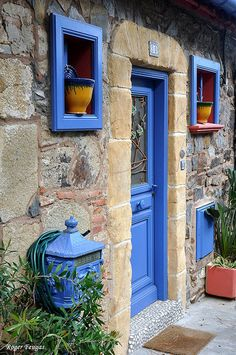 This stone and brick home is accented by a blue door. The color is continued in…