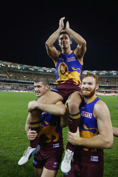 Simon Black of the Lions is chaired off by team mates Jonathan Brown and Daniel Merrett after his 320th game during the round 13 AFL match between the Brisbane Lions and the Geelong Cats at The Gabba on June 23, 2013 in Brisbane, Australia.