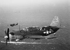 Палубный пикирующий бомбардировщик SB2C-3 «Хэллдайвер»  (Curtiss SB2C-3 Helldiver) 7-й бомбардировочной эскадрильи (VB-7) ВМФ США в полете над кораблями 38-го оперативного соединения 1945
