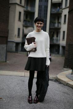 Ming Xi. White sweater, black skirt, black tights.