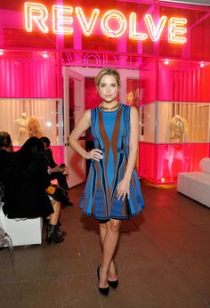 Ashley Benson wears a multi-color, striped dress for the Revolve holiday party at the Grove in L.A.