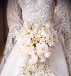 Very formal and sophisticated white and ivory cascade bouquet featuring peonies, garden roses, tea roses, and orchids.